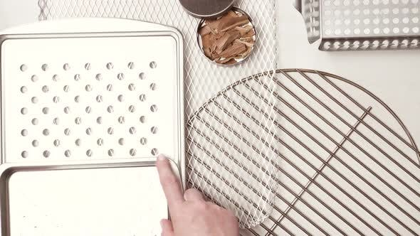 Variety of BBQ grill trays on a white painted wood background