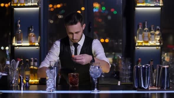 Thumbnail for Bartender Burning Orange Peel for Cocktail