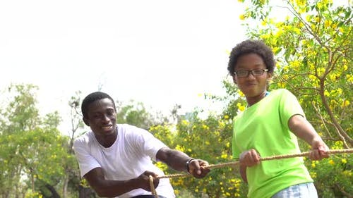 African American Father and Daughter Pulling a Rope Together in Tug of War Competition