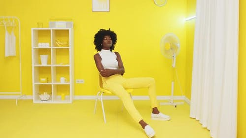 Portrait of Black Woman Sitting On Yellow Chair