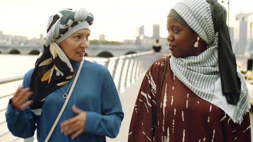 Female Muslim Friends Walking on Embankment