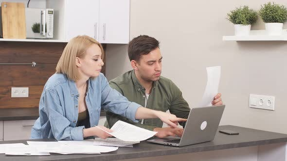 Caucasian Young Couple Reading and Analyzing Bills Sitting at Table