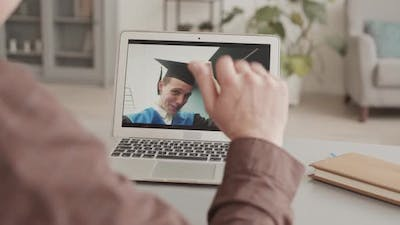 Parent Having Video Call with Son during Graduation Ceremony