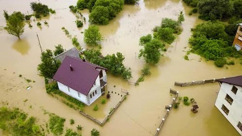 Aerial view of flooded house with dirty water all around it.