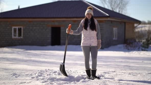 Thumbnail for Junges Mädchen steht mit einer Schaufel im Hinterhof, Frau bereit, Schnee nach Schneefall zu löschen