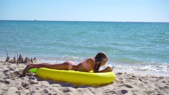 Adorable Girl on Inflatable Air Mattress on the Beach