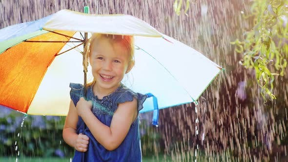 Thumbnail for Carefree Little Girl Under a Colored Umbrella