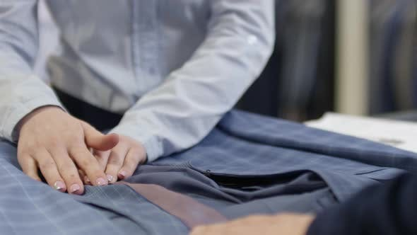 Thumbnail for Hands of Sales Assistant Showing Suit to Customer