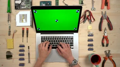 Typing on a MacBook at a desk with craftsman