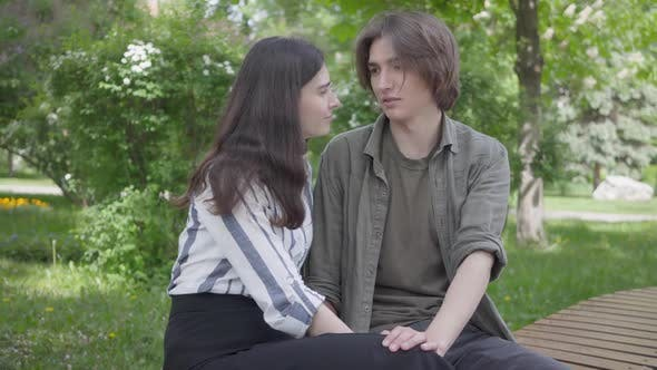Thumbnail for Young Couple in Casual Clothes Sitting at the Bench Talking and Holding Hands. Happy Girl and Boy