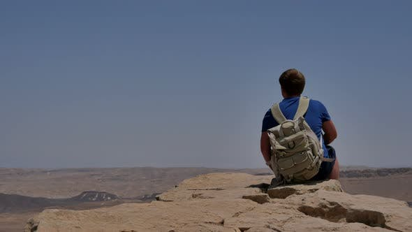 Cover Image for Young Man with Backpack Sitting on Cliff's Edge and Looking at the Desert