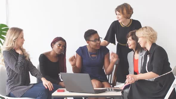 Thumbnail for Positive Women Discuss Organization Plan While Sitting at Table with Laptop
