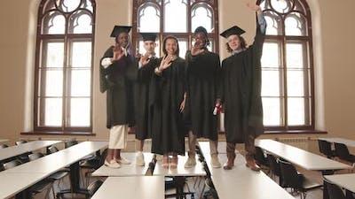 Happy Graduates Standing on School Desks