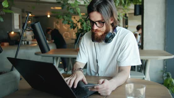 Thumbnail for Man Paying with Credit Card on Laptop in Cafe