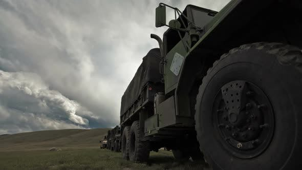 Dollying time-lapse of a stationary military convoy truck.