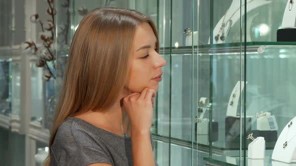 Cover Image for Attractive Young Female Customer Examining Display at the Jewelry Store