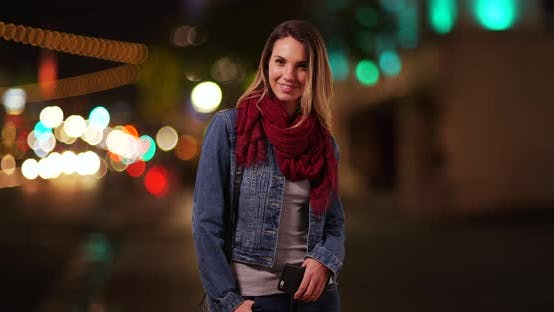 Thumbnail for Portrait of attractive millennial girl smiling at camera on city street at night