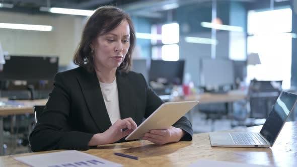 Thumbnail for Serious mittleren Alters Geschäftsfrau Arbeiten auf Tablet im Büro