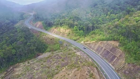 Thumbnail for Drone Flies Over Modern Highway and Shows Driving Car