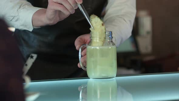 Thumbnail for The Barman at the Bar Makes Cocktail with Ice, Decorating with a Piece of Pineapple