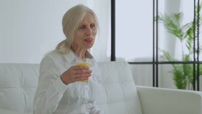 Senior Woman Drinking Orange Juice Sitting on the Couch Old People Retirement and Healthy Lifestyles