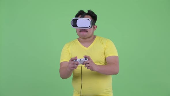 Cover Image for Happy Young Overweight Asian Man Playing Games While Using Virtual Reality Headset