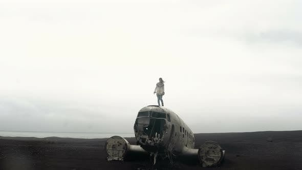 Thumbnail for Young Traveling Woman Standing on the Top of Breaker DC-3 BMC Plane on the Black Beach in Iceland