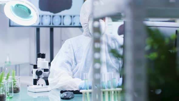 Thumbnail for Biologist Dressed in Protective Coverall and Wearing a Mask Is Lookign at a Microscope