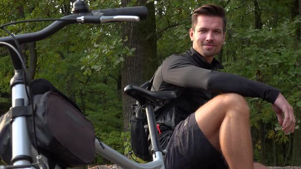 Thumbnail for A Young Handsome Cyclist Sits on a Log Next To His Bike in a Forest and Smiles