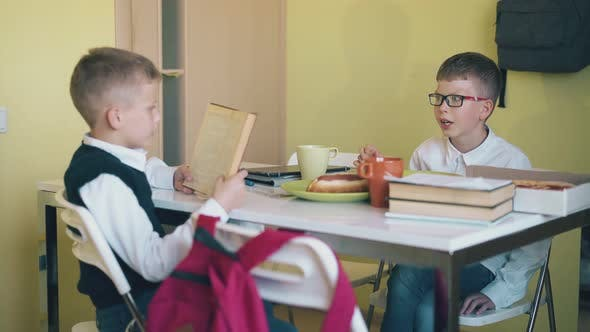 Schoolboy Reads Book To Friend Eating at Table in Canteen