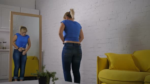 Thumbnail for Anxious Woman Trying To Button Jeans with Effort