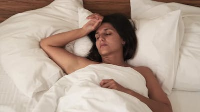 Adult Woman is Sleeping and Starting to Wake Up at Morning