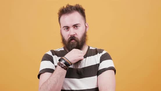 Thumbnail for Portrait of a Young Handsome Man Arranging His Beard and Looking at the Camera