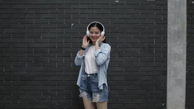 Beautiful Asian woman wears headphones listening to music and dancing.