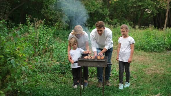 Dad, mom and children fry meat on skewers on the grill. Family picnic in the Park.