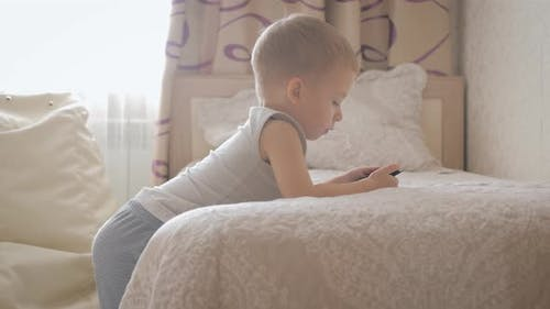 Little Boy Sitting on a Bed and Plays on the Tablet in the Room