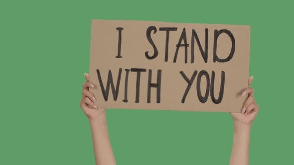 Thumbnail for Female Hands Hold a Poster From a Cardboard Box with the Words I STAND WITH YOU. Protest Against