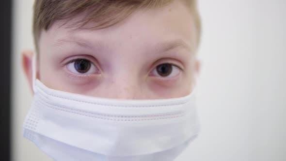 Thumbnail for Ein junger Junge in einer Gesichtsmaske schaut auf die Kamera - Gesicht Detail