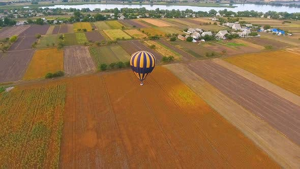 Thumbnail for Hot Air Balloons Landing on Rural Field, Village and River at Background, Aerial