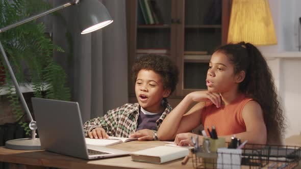 Afro Siblings Studying Online On Laptop