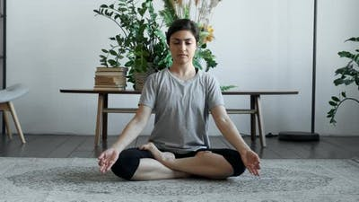 Young female in lotus position doing namaste in living room