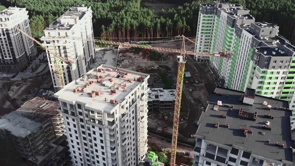 Drone flying over construction site with crane and builders working on unfinished building