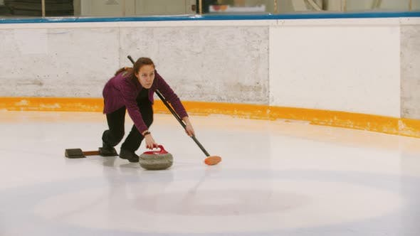 Thumbnail for Curling - a Woman Pushes Off on the Ice Field with a Granite Stone Holding a Brush