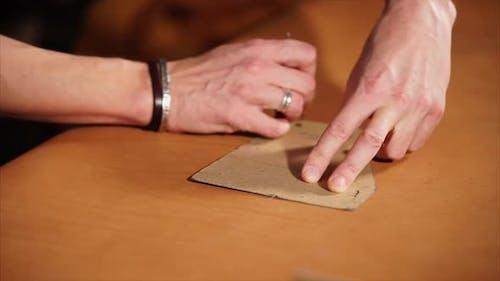 Tailor dessine des lignes sur le morceau de cuir