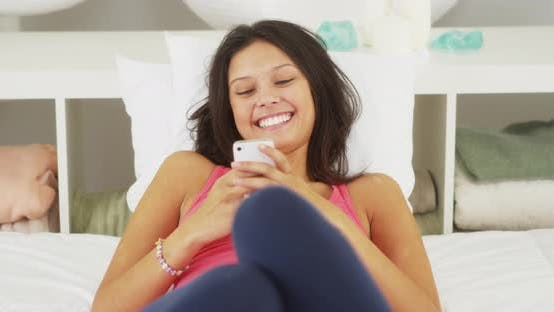 Thumbnail for Hispanic woman laughing and texting on bed