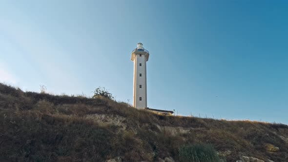 Lighthouse on Sand Dune Against Blue Sky
