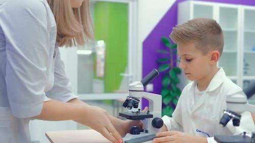 Lehrer hilft Schülern, das Labormikroskop an die Arbeit anzupassen