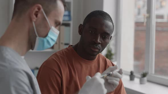 Thumbnail for Man Watching Doctor Preparing for Injection