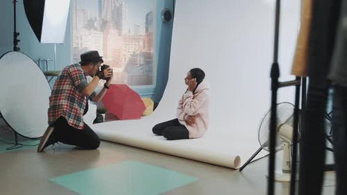 Backstage of the Photo Shoot Black Model Posing on the Floor for a Photographer