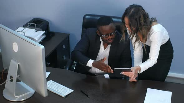 Thumbnail for Business Couple Surfing the Internet in a Digital Tablet in Office